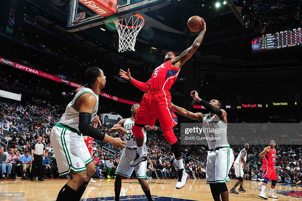 Josh Smith #5 of the Atlanta Hawks rebounds against Jared Sullinger #7, Paul Pierce #34, and Rajon Rondo #9 of the Boston Celtics on January 5, 2013 at Philips Arena in Atlanta, Georgia.