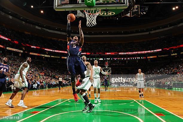 Josh Smith of the Atlanta Hawks shoots a layup against Chris Wilcox of the Boston Celtics on March 29 2013 at the TD Garden in Boston Massachusetts...