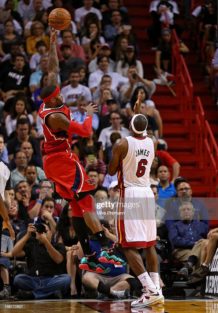 Josh Smith #5 of the Atlanta Hawks shoots over LeBron James #6 of the Miami Heat during a game at American Airlines Arena on December 10, 2012 in Miami, Florida.