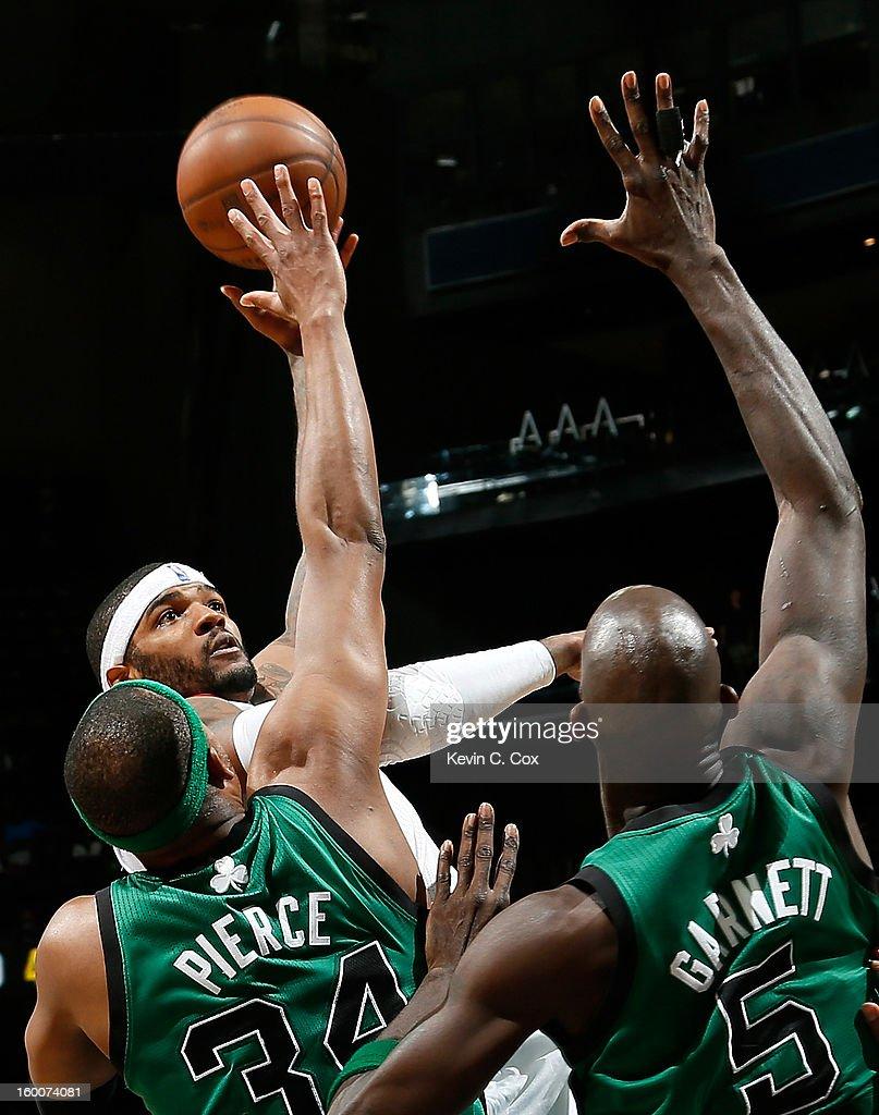 Josh Smith #5 of the Atlanta Hawks shoots over Paul Pierce #34 and Kevin Garnett #5 of the Boston Celtics at Philips Arena on January 25, 2013 in Atlanta, Georgia.