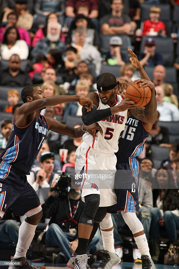 Josh Smith #5 of the Atlanta Hawks wrestles for the ball against Michael Kidd-Gilchrist #14 of the Charlotte Bobcats at the Time Warner Cable Arena on November 23, 2012 in Charlotte, North Carolina.