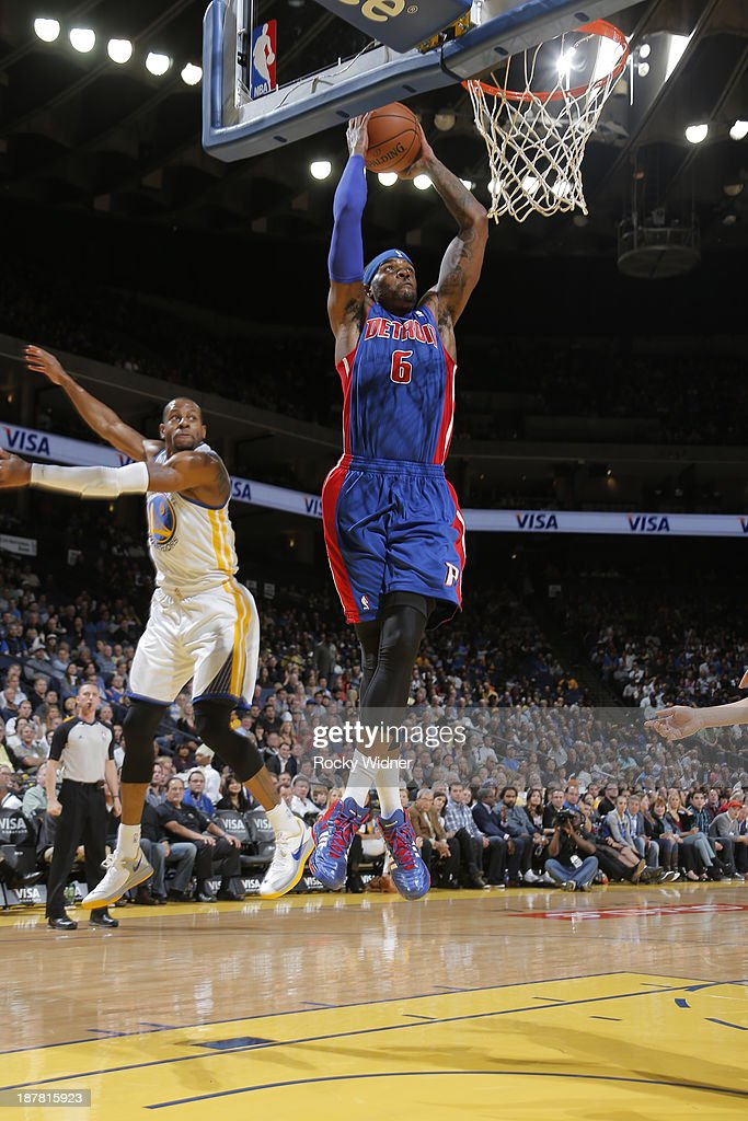 Josh Smith #6 of the Detroit Pistons dunks against Andre Iguodala #9 of the Golden State Warriors on November 12, 2013 at Oracle Arena in Oakland, California.