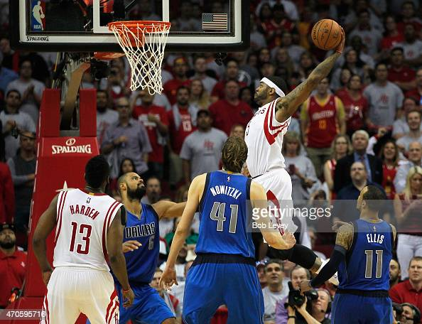 Josh Smith of the Houston Rockets drives baseline for a dunk past Monta Ellis of the Dallas Mavericks as well as Dirk Nowitzki and Tyson Chandler as...
