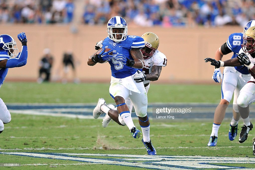 Josh Snead #9 of the Duke Blue Devils avoids a tackle by John Loughery #11 of the Elon Phoenix at Wallace Wade Stadium on August 30, 2014 in Durham, North Carolina.
