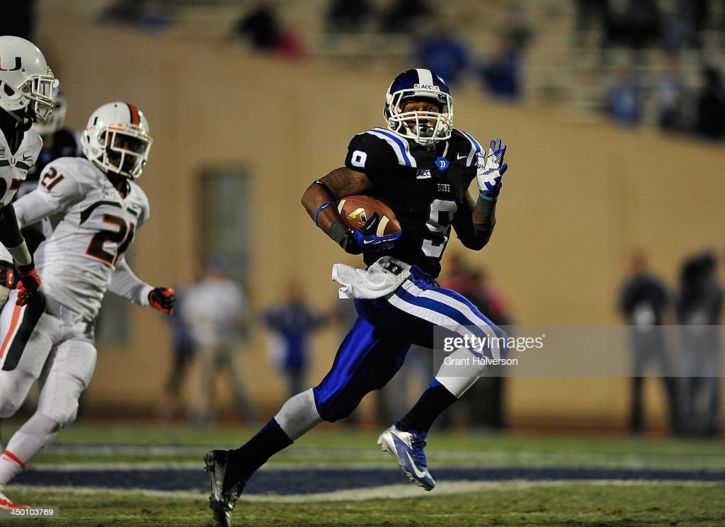 Josh Snead #9 of the Duke Blue Devils breaks away from Jared Goldenberg #53 and Antonio Crawford #21 of the Miami Hurricanes during play at Wallace Wade Stadium on November 16, 2013 in Durham, North Carolina. Duke won 48-30.