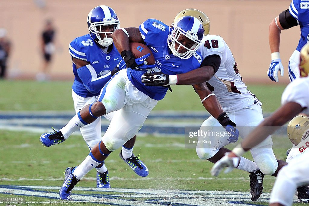 Josh Snead #9 of the Duke Blue Devils is tackled by Corey Mitchell #48 of the Elon Phoenix at Wallace Wade Stadium on August 30, 2014 in Durham, North Carolina.