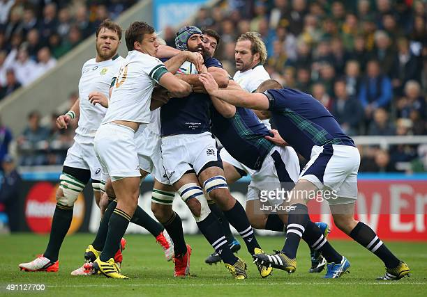 Josh Strauss of Scotland is held up by Handre Pollard Francois Louw and Schalk Burger of South Africa during the 2015 Rugby World Cup Pool B match...