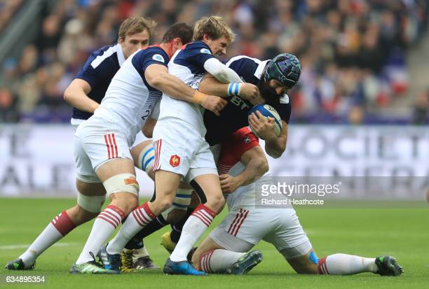 Josh Strauss of Scotland is wrapped up by Yoann Maestri Baptiste Serin and Guilhem Guirado of France during the RBS Six Nations match between France...