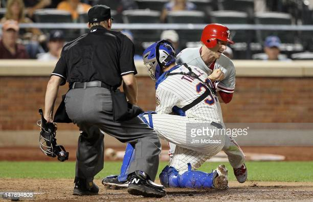 Josh Thole of the New York Mets tags out Mike Fontenot of the Philadelphia Phillies in the eighth inning at Citi Field on July 5 2012 in the Flushing...