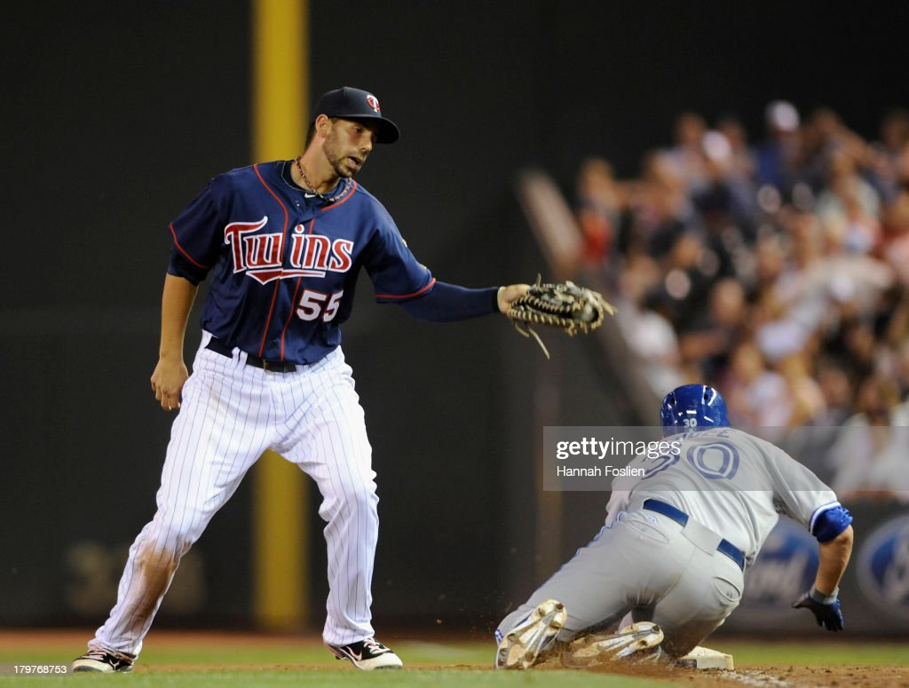 Josh Thole #30 of the Toronto Blue Jays is safe at first base as Chris Colabello #55 of the Minnesota Twins attempts to apply the tag during the seventh inning of the game on September 6, 2013 at Target Field in Minneapolis, Minnesota. The Blue Jays defeated the Twins 6-5.