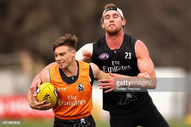 Josh Thomas is tackled by Lachlan Keeffe during a Collingwood Magpies AFL training session at Olympic Park on July 9 2014 in Melbourne Australia