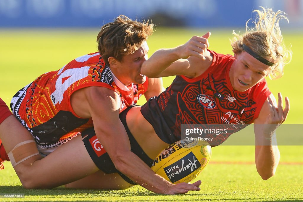 Josh Wagner of the Demons handballs whilst being tackled by David Swallow of the Suns during the round ten AFL match between the Melbourne Demons and the Gold Coast Suns at Traeger Park on May 27, 2017 in Alice Springs, Australia.