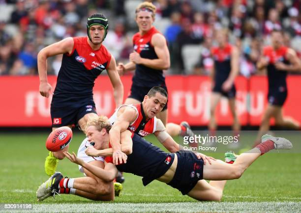 Josh Wagner of the Demons handballs whilst being tackled by Shane Savage of the Saints during the round 21 AFL match between the Melbourne Demons and...