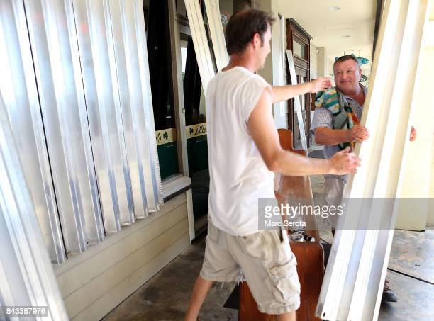 Josh Walker and Zoli Bedo installs hurricane shutters at Dillon's Pub in the Florida Keys on September 6 2017 in Islamorada Florida Hurricane Irma...
