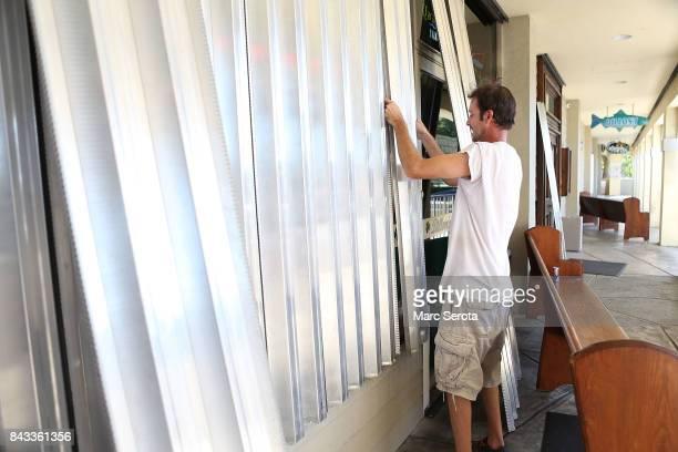 Josh Walker installs hurricane shutters at Dillon's Pub in the Florida Keys on September 6 2017 in Islamorada Florida Hurricane Irma has grown to a...