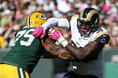 Josh Walker of the Green Bay Packers blocks Nick Fairley of the St Louis Rams in the second quarter at Lambeau Field on October 11 2015 in Green Bay...