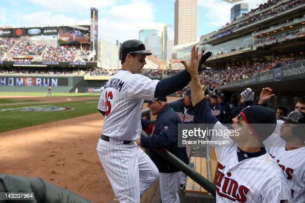 Josh Willingham and Justin Morneau of the Minnesota Twins in the dugout following a home run against the Los Angeles Angels on April 9 2012 at Target...