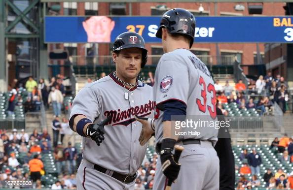Josh Willingham of the Minnesota Twins celebrates his first inning home run to left field with teammate Justin Morneau during the game against the...