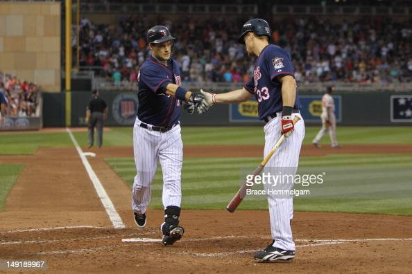 Josh Willingham of the Minnesota Twins celebrates his home run with Justin Morneau against the Baltimore Orioles on July 18 2012 at Target Field in...