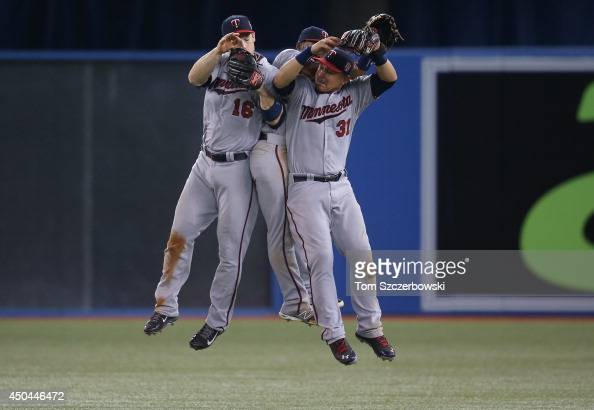 Josh Willingham of the Minnesota Twins celebrates their victory with Danny Santana and Oswaldo Arcia during MLB game action against the Toronto Blue...