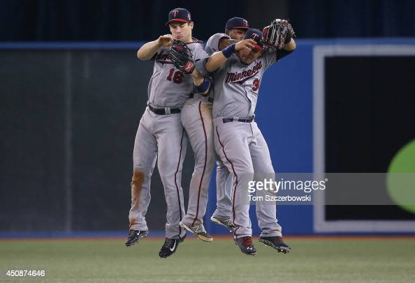 Josh Willingham of the Minnesota Twins celebrates their victory with Danny Santana and Oswaldo Arcia during an MLB game against the Toronto Blue Jays...