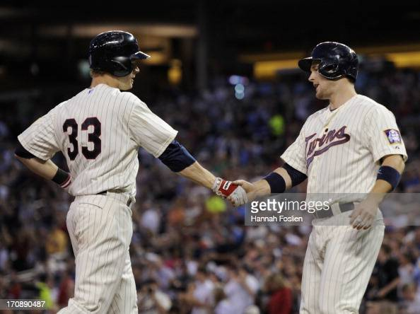 Josh Willingham of the Minnesota Twins congratulates teammate Justin Morneau on a two run home run against the Chicago White Sox during the sixth...