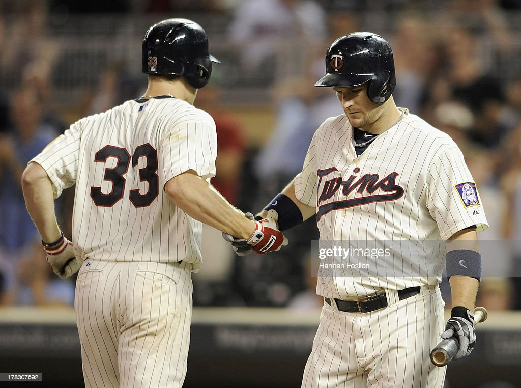 Josh Willingham #16 of the Minnesota Twins congratulates teammate Justin Morneau #33 on a solo home run against the Kansas City Royals during the ninth inning of the game on August 28, 2013 at Target Field in Minneapolis, Minnesota. The Royals defeated the Twins 8-1.