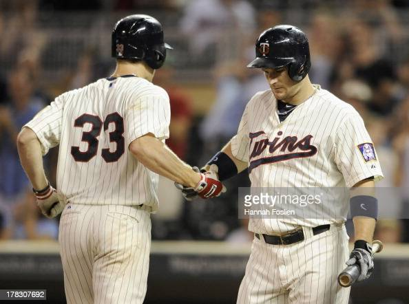 Josh Willingham of the Minnesota Twins congratulates teammate Justin Morneau on a solo home run against the Kansas City Royals during the ninth...