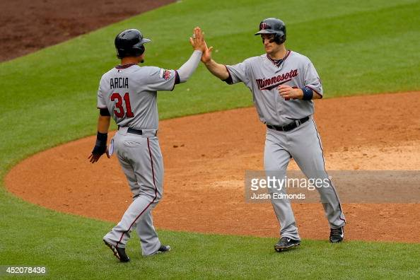 Josh Willingham of the Minnesota Twins gets a high five from Oswaldo Arcia after scoring during the ninth inning against the Colorado Rockies at...