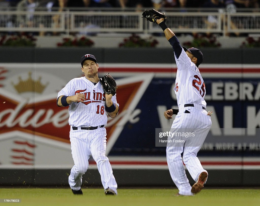 <a gi-track='captionPersonalityLinkClicked' href=/galleries/search?phrase=Josh+Willingham&family=editorial&specificpeople=537640 ng-click='$event.stopPropagation()'>Josh Willingham</a> #16 of the Minnesota Twins reacts as teammate Pedro Florimon #25 makes a catch during the fifth inning of the game against the Cleveland Indians on August 13, 2013 at Target Field in Minneapolis, Minnesota.