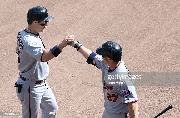 Josh Willingham of the Minnesota Twins scores on Justin Morneau double to deep center and is congratulated by teammate Chris Parmelle during the...