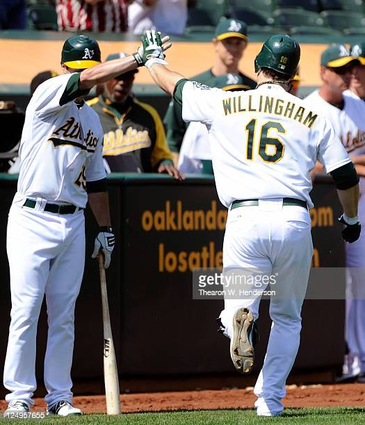 Josh Willingham of the Oakland Athletics celebrates with Scott Sizemore after hitting a home run against the Los Angeles Angels of Anaheim in third...