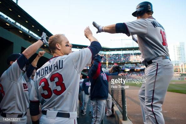 Josh Willingham shows emotion with Justin Morneau of the Minnesota Twins after scoring a run during the game against the Baltimore Orioles at Oriole...