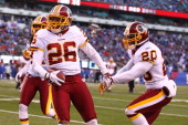 Josh Wilson of the Washington Redskins celebrates his interception with Oshiomogho Atogwe during their game against the New York Giants at MetLife...