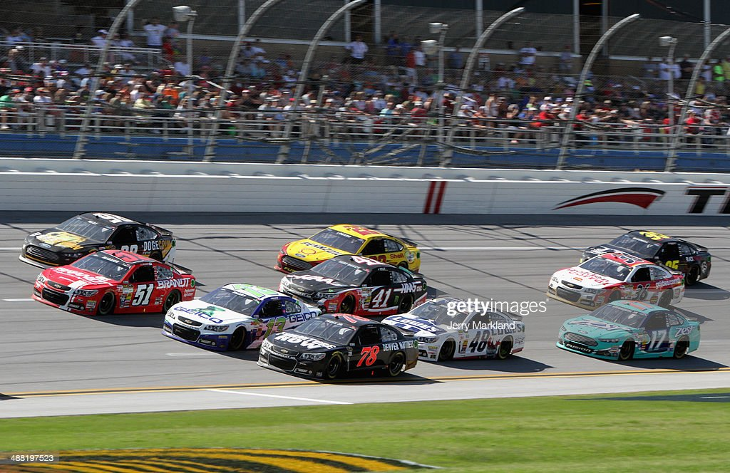 Josh Wise, driver of the #98 Dogecoin / Reddit.com Ford, Justin Allgaier, driver of the #51 Brandt Professional Agriculture Chevrolet, Casey Mears, driver of the #13 GEICO Chevrolet, and Martin Truex Jr., driver of the #78 Furniture Row Chevrolet, lead a pack of cars during the NASCAR Sprint Cup Series Aaron's 499 at Talladega Superspeedway on May 4, 2014 in Talladega, Alabama.