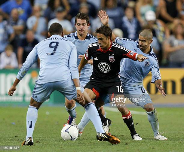 Josh Wolff of the DC United tries to clear the ball away from Teal Bunbury Paulo Nagamura and Michael Thomas of the Sporting Kansas City in the...