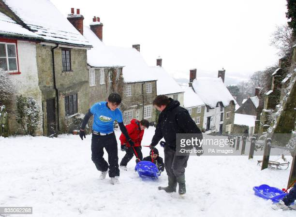 Josh Wyman his brother Danny and his friend Alex Rivers pull little Louis Wyman up the iconic Gold Hill in Shaftesbury Dorset on a sledge where it...