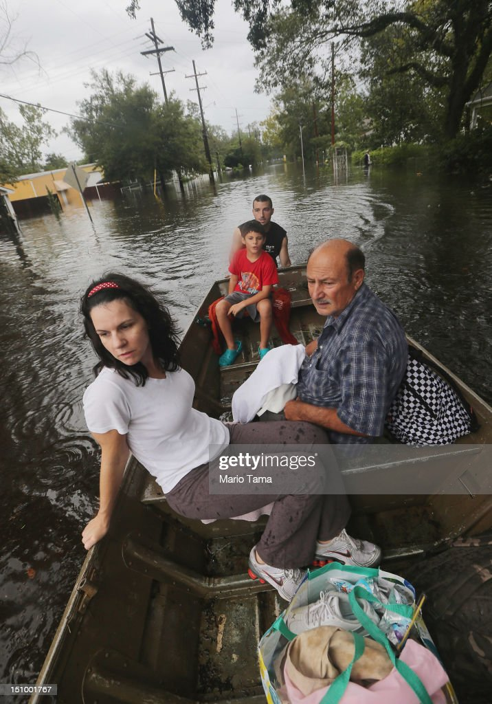 Joshua Barbot (BACK) rescues family members (L to R) Christie, Ethan and Larry Trumbaturi from their flooded home in his boat on August 30, 2012 in Slidell, Louisiana. Hurricane Isaac storm surge caused flooding in Slidell this morning on the north shore of Lake Ponchartrain. The large Level 1 hurricane slowly moved across southeast Louisiana, dumping huge amounts of rain and knocking out power to Louisianans in scattered parts of the state. The weather system has now been downgraded to a tropical storm but is still producing heavy rains and flooding as it moves north.