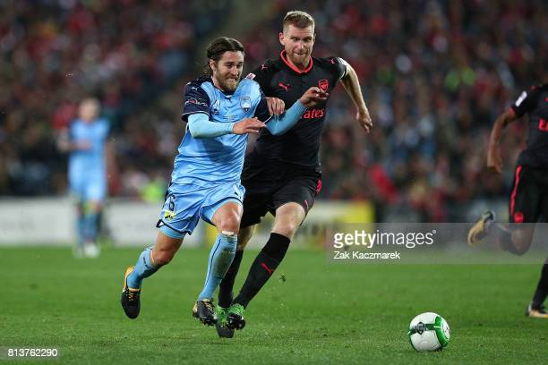 Joshua Brillante of Sydney FC competes with Per Mertesacker of Arsenal during the match between Sydney FC and Arsenal FC at ANZ Stadium on July 13...