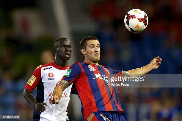 Joshua Brillante of the Jets contests the header against Bruce Djite of Adelaide United during the round 27 ALeague match between the Newcastle Jets...
