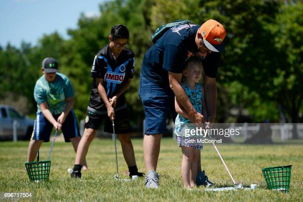 Joshua Bruce helps his daughter Harleigh Bruce as she hits a bucket of golf balls at Del Mar Park on June 14 in Aurora Colorado Free summer...
