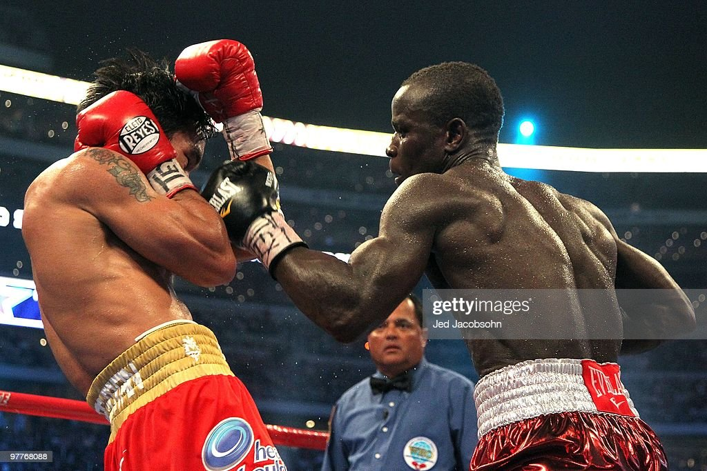 Joshua Clottey of Ghana throws a left to the face of Manny Pacquiao of the Philippines during the WBO welterweight title fight at Cowboys Stadium on...
