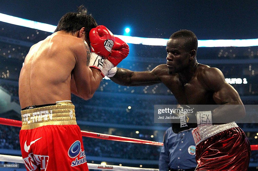 Joshua Clottey of Ghana throws a right to the face of Manny Pacquiao of the Philippines during the WBO welterweight title fight at Cowboys Stadium on...