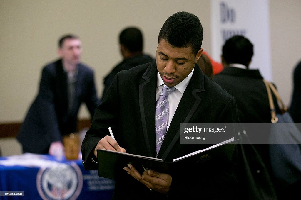 Joshua Cratic takes notes on company booths he wants to visit at a National Career Fairs job fair in Arlington, Virginia, U.S., on Wednesday, Jan. 30, 2013. The U.S. Labor Department is scheduled to release initial jobless claims data on Jan. 31. Photographer: Andrew Harrer/Bloomberg via Getty Images