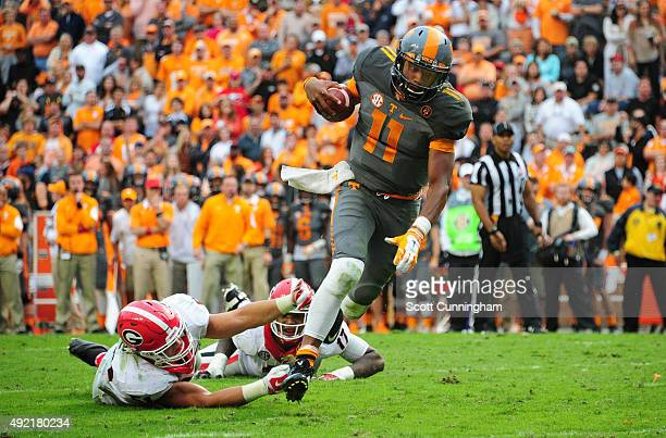 Joshua Dobbs of the Tennessee Volunteers breaks away for a touchdown from a tackle attempt by Jake Ganus of the Georgia Bulldogs on October 10 2015...