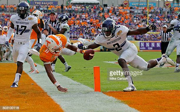 Joshua Dobbs of the Tennessee Volunteers dives past the defense of Traveon Henry of the Northwestern Wildcats to score a touchdown during the second...