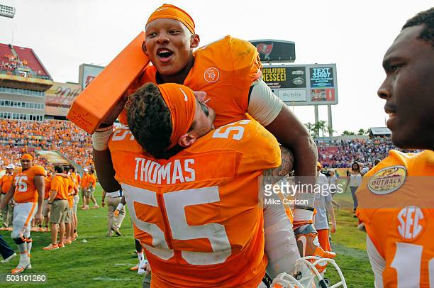 Joshua Dobbs of the Tennessee Volunteers is lifted by Coleman Thomas of the Tennessee Volunteers as they celebrate a win over Northwestern Wildcats...