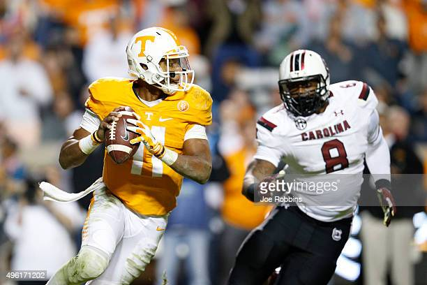 Joshua Dobbs of the Tennessee Volunteers looks to pass while under pressure from Marquavius Lewis of the South Carolina Gamecocks in the second half...