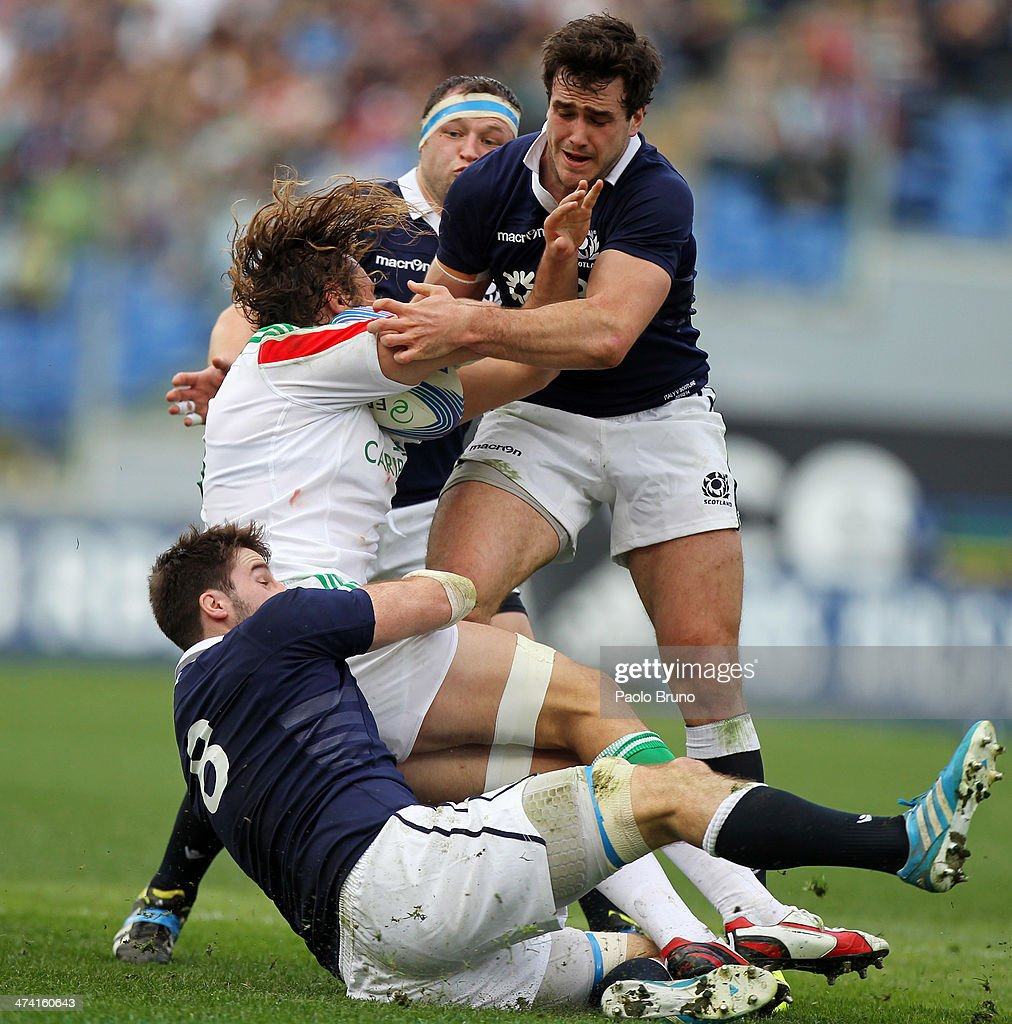 Joshua Furno (C) of Italy is tackled by <a gi-track='captionPersonalityLinkClicked' href=/galleries/search?phrase=Johnnie+Beattie&family=editorial&specificpeople=4355668 ng-click='$event.stopPropagation()'>Johnnie Beattie</a> and Alex Dunbar of Scotland players during the RBS Six Nations match between Italy and Scotland at Stadio Olimpico on February 22, 2014 in Rome, Italy.