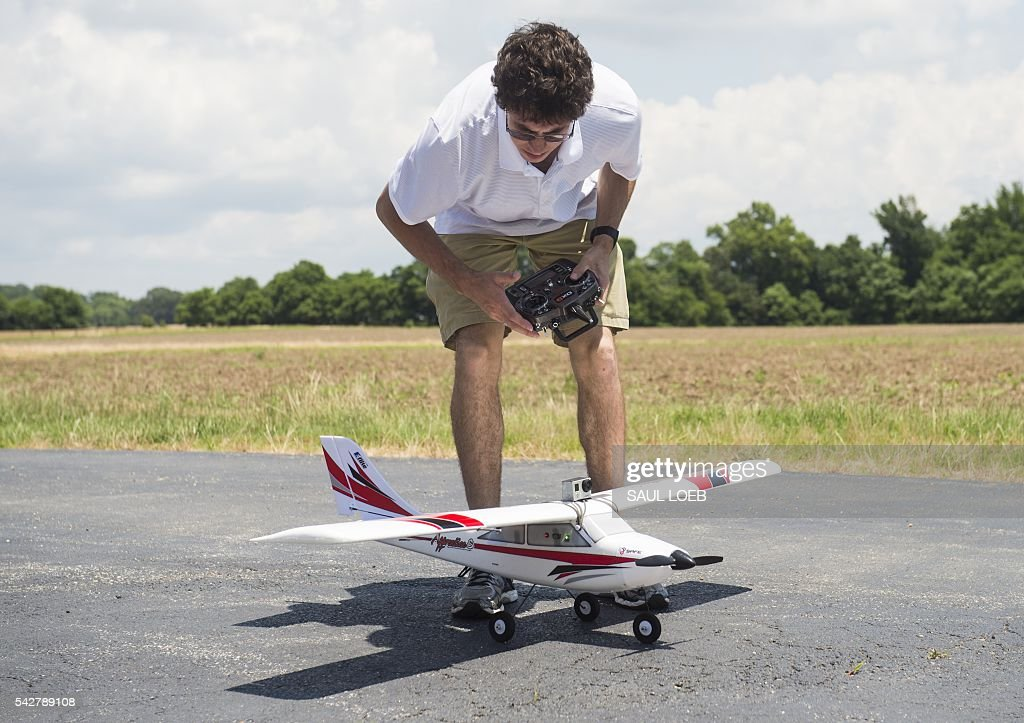 Joshua Gaus, a mechanical engineering student at the University of Maryland, examines a remote-controlled airplane that he has outfitted with autonomous flying controls so that it can fly itself prior to a flight at a testing site for the University of Maryland's Unmanned Aircraft Systems (UAS) programs in Bushwood, Maryland, June 24, 2016. The Federal Aviation Administration has unveiled new rules that clear the way for small, commercial drones to operate across US airspace. Drone operators will be allowed to fly commercial craft weighing less than 55 pounds (25 kilograms) during daylight hours, provided they can maintain a clear view of the drone at all times. / AFP / SAUL
